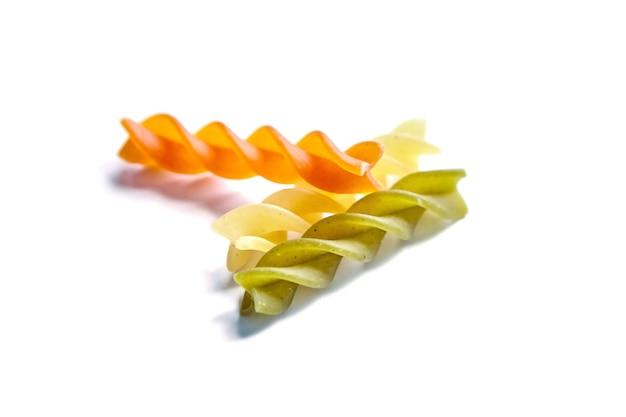Ungekochte fusilli tricolore nudeln isoliert auf einem weißen Premium Fotos
