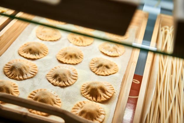 Ungekochte raviolimischung auf hölzernem behälter im schaufenster. Premium Fotos