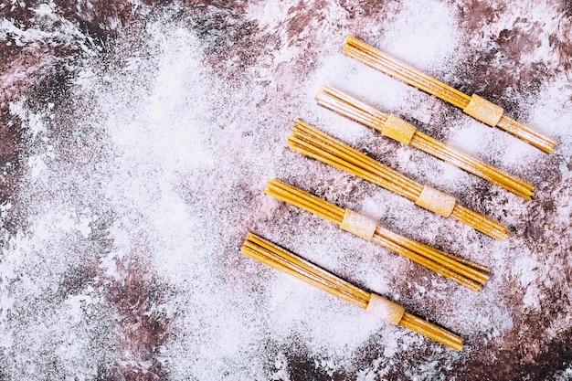 Ungekochte rohe spaghetti auf brauner oberfläche. Kostenlose Fotos