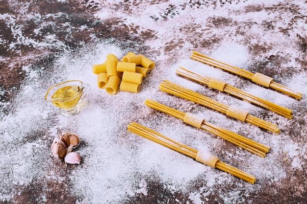 Ungekochte rohe spaghetti und makkaroni auf hölzernem küchentisch. Kostenlose Fotos