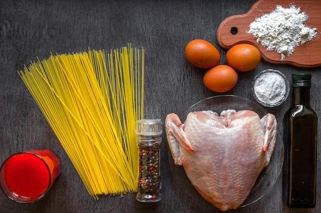 Ungekochte spaghetti und rohes huhn an bord. Premium Fotos