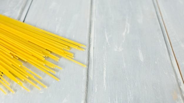 Ungekochte spaghettis mit hölzernem hintergrund Kostenlose Fotos