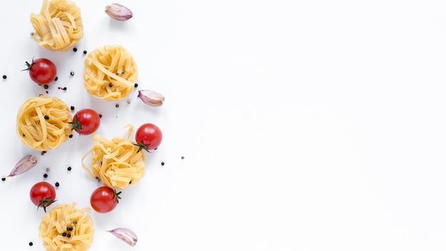 Ungekochte tagliatelle-nudeln; kirschtomate; knoblauchzehe; schwarzer pfeffer getrennt über weißem hintergrund mit platz für text Kostenlose Fotos