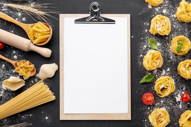 Ungekochte teigwarenzusammenstellung mit mehl auf schwarzem hintergrund mit klemmbrettmodell Kostenlose Fotos