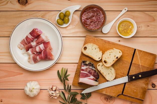 Ungekochter speck; salsa-sauce; oliven; toastbrot; knoblauch; hineingegossenes öl und oliven auf holztisch Kostenlose Fotos
