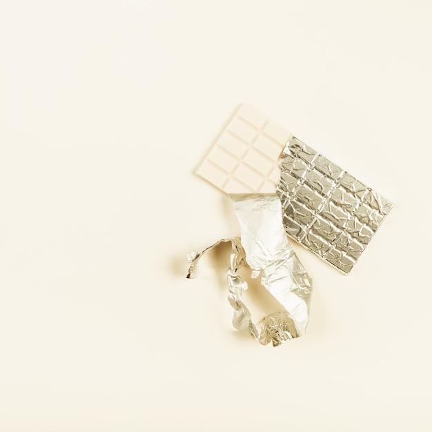 Ungepackte weiße schokolade in der folie auf farbigem hintergrund Kostenlose Fotos