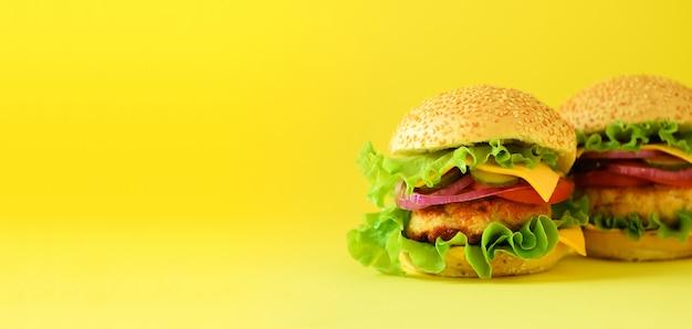 Ungesunde burger mit rindfleisch, käse, kopfsalat, zwiebel, tomaten auf gelbem hintergrund. essen zum mitnehmen. ungesundes diätkonzept. Premium Fotos