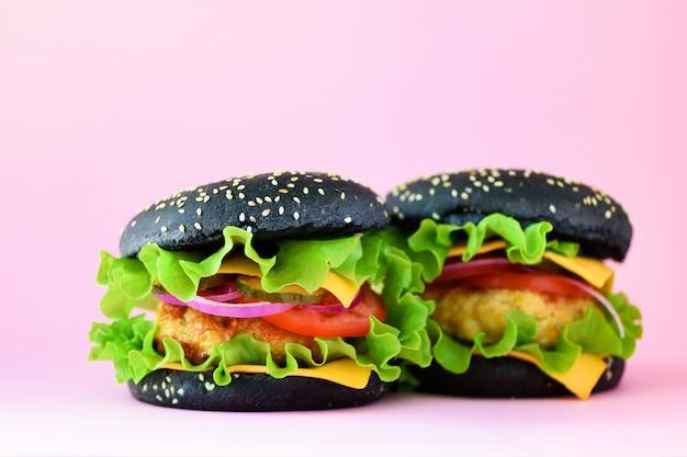 Ungesunde schwarze burger mit rindfleisch, käse, kopfsalat, zwiebel, tomaten auf rosa hintergrund. essen zum mitnehmen. konzept der ungesunden diät und kopienraum Premium Fotos