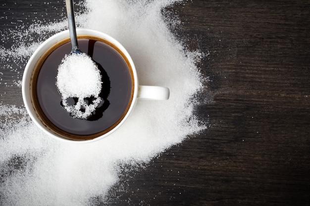 Ungesundes weißzuckerkonzept. schädellöffel mit zucker und tasse schwarzen kaffees auf hölzernem hintergrund Premium Fotos