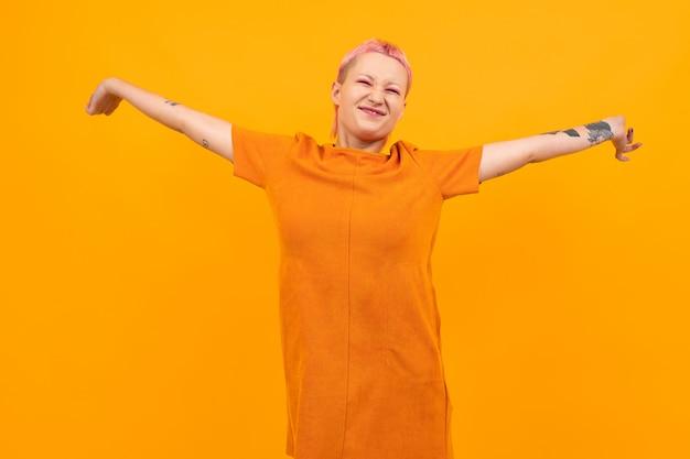 Ungewöhnliche hübsche frau mit kurzen rosa haaren und tätowierungslächeln lokalisiert auf orange hintergrund Premium Fotos