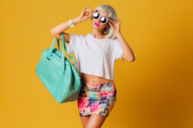 Ungewöhnliches hübsches blondes mädchen des modestudio-porträts in der kurzen partyperücke, im weißen oberteil und im sexy rock, die innen auf gelbem hintergrund aufwerfen. sonnige positive emotionen, stilvolle sonnenbrille. Kostenlose Fotos