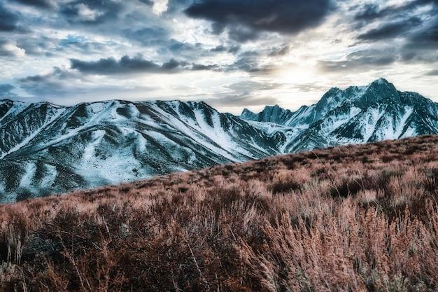Unglaubliche aufnahme von schneebedeckten bergen, wunderschöner bewölkter himmel über ihnen Kostenlose Fotos
