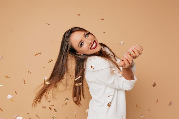 Unglaubliches weibliches modell mit dem schönen lächeln und dem langen hellbraunen haar, das weiße jacke trägt, die auf beige wand mit confeti aufwirft und sich auf geburtstagsfeier vorbereitet Kostenlose Fotos