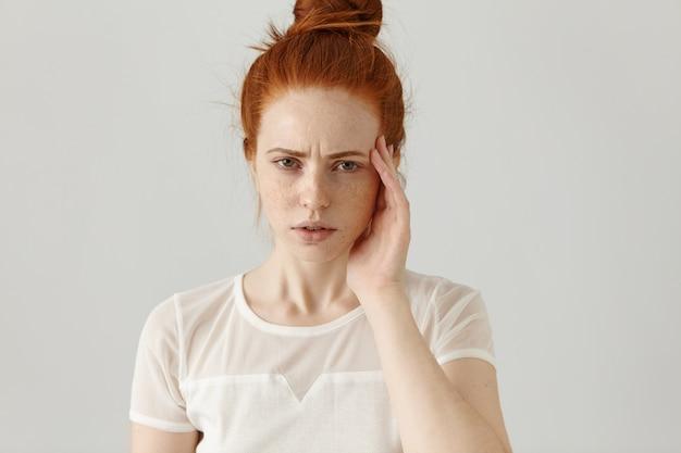 Unglücklich gestresste junge rothaarige frau mit haarknoten, die das gesicht berührt, während sie unter starken kopfschmerzen leidet, die stirn runzelt und mit angespanntem und schmerzhaftem gesichtsausdruck schaut. körpersprache Kostenlose Fotos