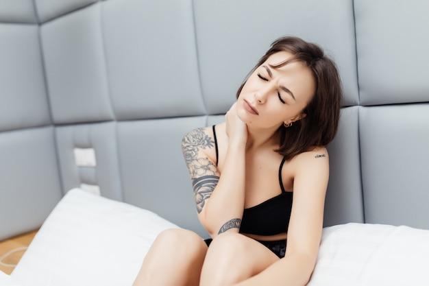 Unglücklich müde junge schöne frau haben nackenschmerzen, die morgens in ihrem bett aufwachen Kostenlose Fotos
