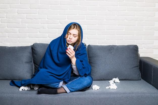 Unglücklich verärgert sitzt müde frau auf einem sofa zu hause, leidet an einer erkältung und benutzt servietten, wird kalt Kostenlose Fotos