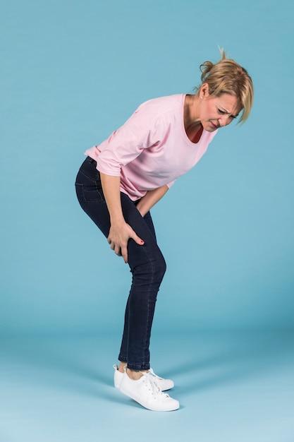 Unglückliche frau, die ihre wunden oberschenkelmuskeln auf blauem hintergrund hält Kostenlose Fotos