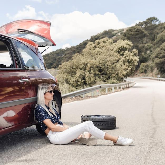 Unglückliche frau, die nahe dem aufgegliederten auto auf kurvenreicher straße sitzt Kostenlose Fotos