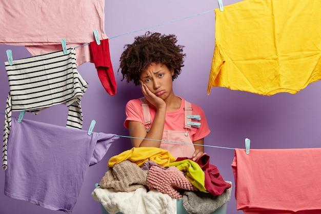 Unglückliche junge frau mit einem afro, der mit wäsche im overall aufwirft Kostenlose Fotos