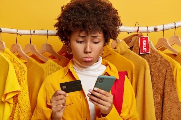 Unglückliche lockige frau verwendet kreditkarte und smartphone für online-shopping traurig Kostenlose Fotos