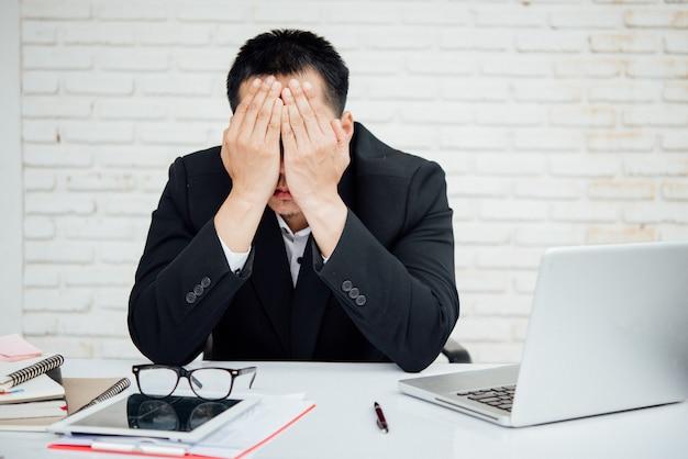 Unglückliche wirtschaftler des geschäftsmannes, die im büro sitzen Kostenlose Fotos