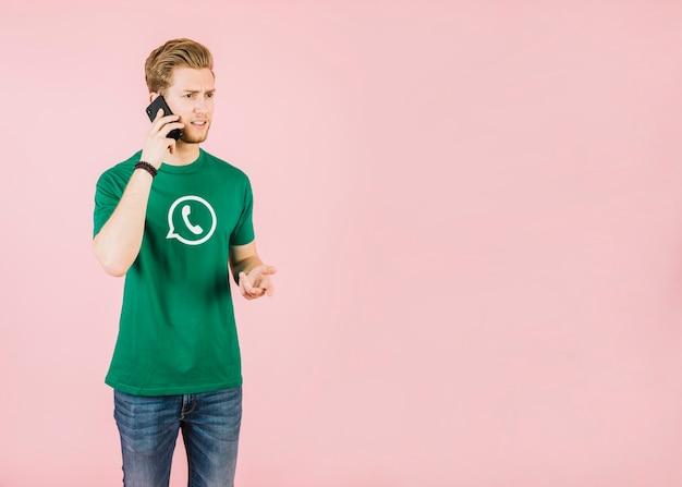 Unglücklicher junger mann, der am handy gegen rosa hintergrund spricht Kostenlose Fotos