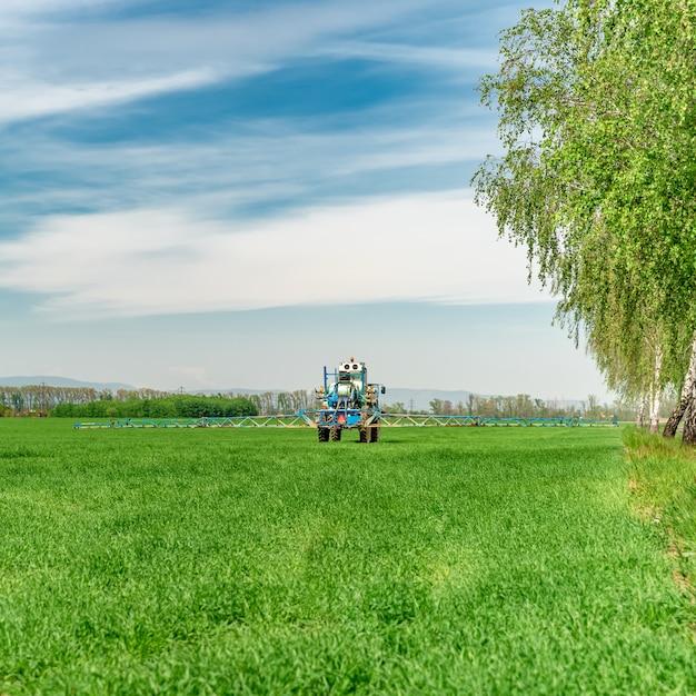 Unkraut auf einem feld von einem traktor mit einem sprühgerät besprühen Premium Fotos