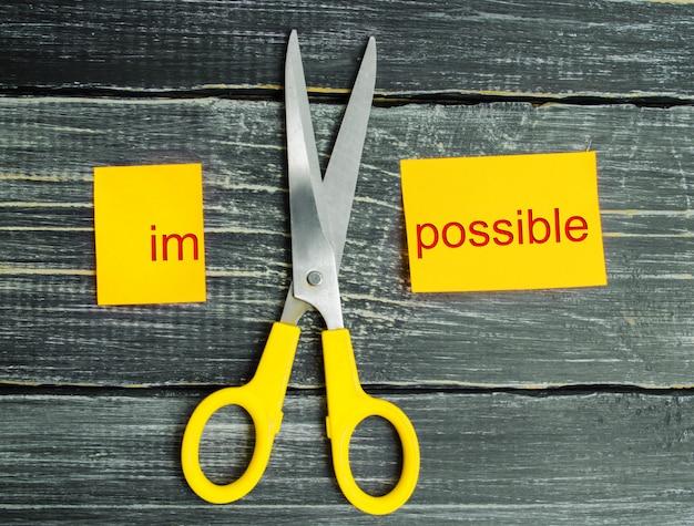 Unmöglich ist mögliches konzept. karte mit dem text unmöglich, schnitt schere ein wort zu ihnen. Premium Fotos