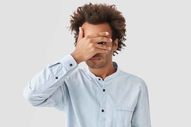 Unrasierter junger lockiger mann bedeckt die augen mit der handfläche, versucht sich zu verstecken, schaut durch die finger Kostenlose Fotos