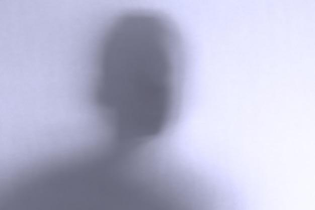 Unscharf gestelltes gruseliges geistergesicht hinter einem weißen glas Premium Fotos