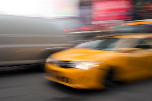 Unscharfe ansicht des gelben taxis bewegend in times square, manhattan, new york city, staat new york, usa Premium Fotos