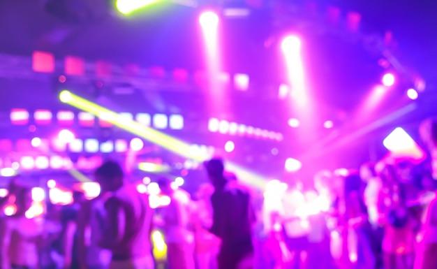 Unscharfe leute, die am musiknachtfestivalereignis tanzen Premium Fotos