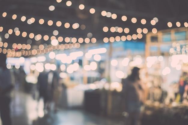 Unscharfe nachtmarktfestivalleute, die auf straße gehen Premium Fotos