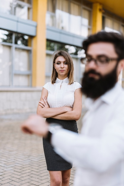 Unscharfer junger geschäftsmann, der zeit auf armbanduhr mit überzeugter geschäftsfrau im hintergrund überprüft Kostenlose Fotos