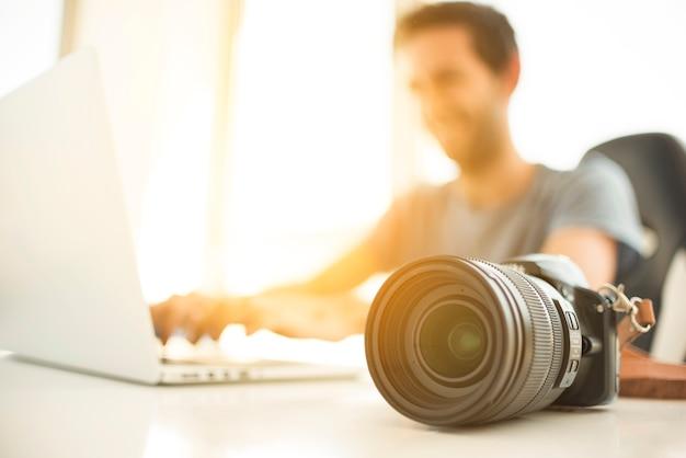 Unscharfer mann, der laptop hinter dslr kamera auf schreibtisch verwendet Kostenlose Fotos