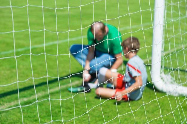 Unscharfes bild eines jungen verletzten männlichen fußball- oder fußballspielers, der behandelt wird Premium Fotos