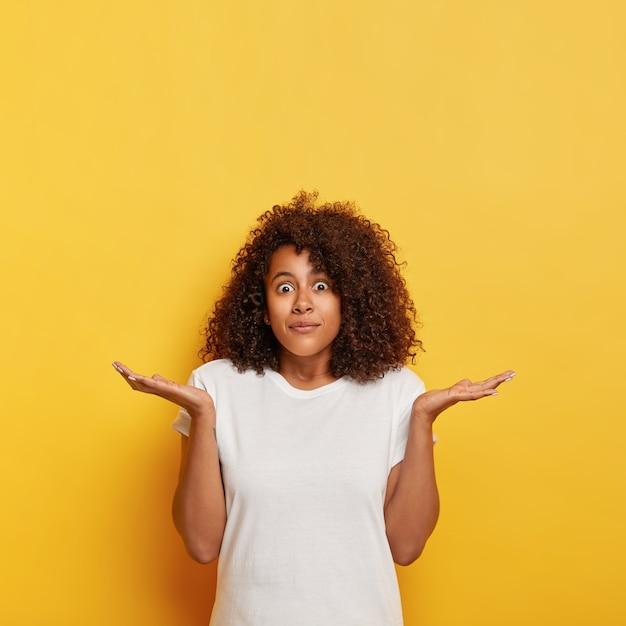 Unsichere verwirrte studentin spreizt die handflächen zur seite, starrt mit verwanzten augen, ist ahnungslos und ahnungslos, hat dunkles lockiges haar, trägt ein weißes t-shirt, posiert an der gelben wand und hat freien platz nach oben Kostenlose Fotos