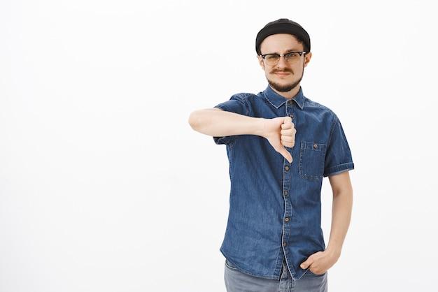 Unsicherer unzufriedener süßer junger mann in schwarzer mütze und brille, der grinst und daumen nach unten zeigt, weil er es nicht mag, mit freunden uneinigkeit auszudrücken, während er über das thema spricht Kostenlose Fotos
