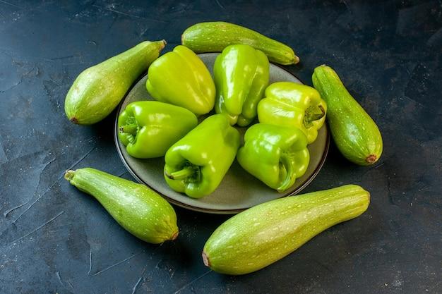 Unteransicht verschiedene größen zucchini um grüne paprika auf grauer runder platte auf dunkler oberfläche Kostenlose Fotos