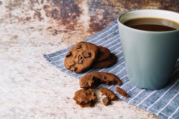 Unterbrochene plätzchen mit tasse kaffee auf rustikalem hintergrund Kostenlose Fotos