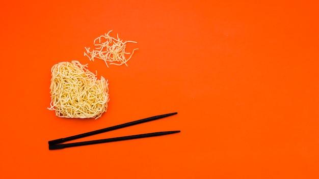 Unterbrochene trockene sofortige nudeln mit essstäbchen über orange hintergrund Kostenlose Fotos