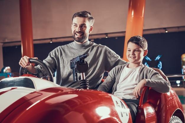 Unterhaltener lächelnder vater und sohn, die auf spielzeugauto sitzt Premium Fotos