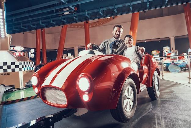 Unterhaltener lächelnder vater und sohn, die auf spielzeugauto sitzt. Premium Fotos