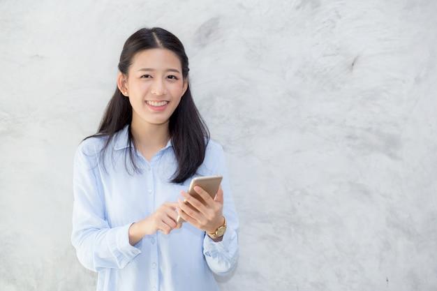 Unterhaltungstelefon und -lächeln der schönen asiatischen frau, die auf zementhintergrund steht ,. Premium Fotos