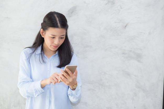 Unterhaltungstelefon und -lächeln der schönen asiatischen frau, die auf zementhintergrund steht Premium Fotos