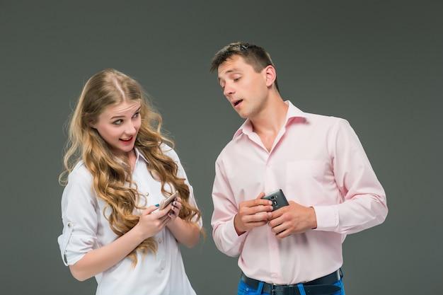 Unternehmenskonzept. die zwei jungen kollegen, die handys auf grauem hintergrund halten Kostenlose Fotos