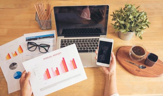 Unternehmenskonzept. junge schöne frau mit laptop und lesedokument bericht an ihrem tisch. Premium Fotos