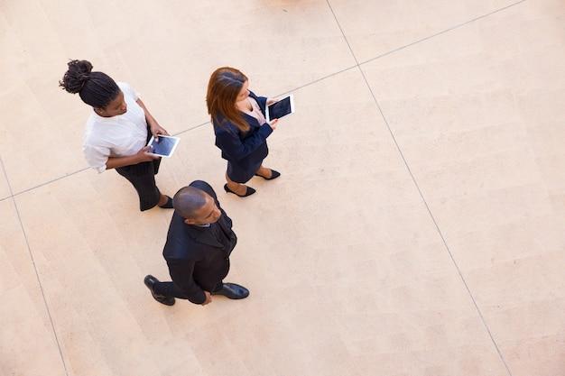 Unternehmensleiter und seine weiblichen assistenten, die durch büro gehen Kostenlose Fotos