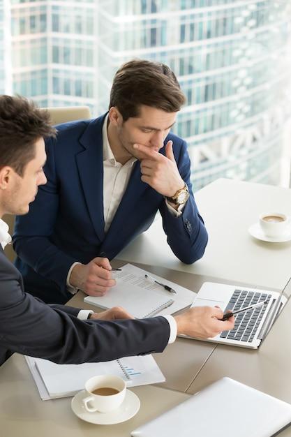 Unternehmer diskutieren arbeitsergebnisse beim treffen Kostenlose Fotos