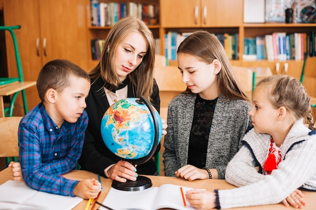 Unterrichtende geografie der jungen frau zum schüler mit kugel Kostenlose Fotos